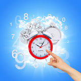 Finger points to alarm clock. With figures and gears. Blue sky background Stock Photos