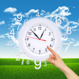 Finger points to clock face with figures. On background of green grass and blue sky Royalty Free Stock Photos