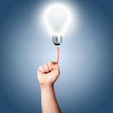 Finger points to light bulb. Man's finger point to light bulb that is turn on. Concept for new idea Royalty Free Stock Photo