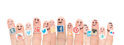 Finger with popular social media logos printed on paper. Royalty Free Stock Photos