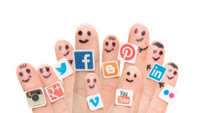Finger with popular social media logos printed on paper. Stock Images