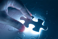 Finger press on blank piece of jigsaw puzzle, conceptual image Stock Photography