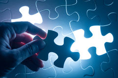 Finger press on blank piece of jigsaw puzzle, conceptual image Royalty Free Stock Images