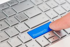 A finger press blue Research button on laptop keyboard stock photography