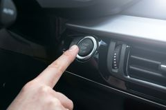 Finger press button functions car engine start and stop in motor vehicle for pre start checklist concept. Modern car interior. Details. Soft lighting Stock Images