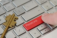 A finger press a button with text Restore on a keyboard.  Stock Photos