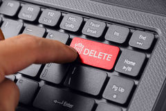 Finger press DELETE button. Gesture of a hand finger pressing DELETE on a laptop keyboard Stock Photo