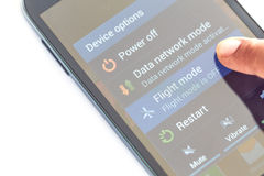 Finger press flight mode button on smartphone Royalty Free Stock Photos