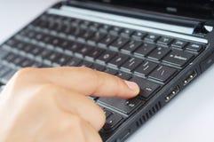 A finger press keyboard enter button. A finger press enter button isolated with keyboard background Stock Images