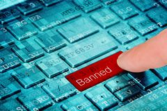A finger press red Bunned button on blue digital laptop keyboard stock images
