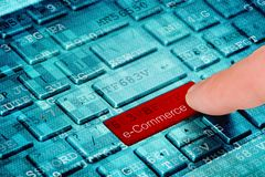A finger press red e-Commerce button on blue digital laptop keyboard.  royalty free stock photos