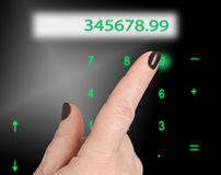 The finger presses the digits of an keyboard. Female finger presses the greenish numbers on the keyboard. Just above the display with numbers Royalty Free Stock Image