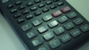 Finger presses the engineering calculator buttons. Closeup shot stock video