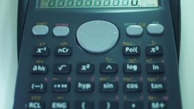 Finger presses the engineering calculator buttons. Closeup shot stock footage