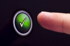 Finger presses touchscreen green tick button Stock Photo