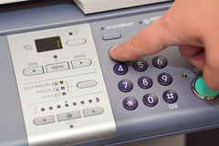 Finger pressing the buttons. The finger pressing the buttons of the copier Royalty Free Stock Images