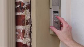 Hand entering code on keypad - garage door opener - home security. Finger pressing buttons on a coded keypad used on a garage door entrance to a home - security stock video