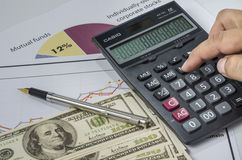 Finger pressing on a calculator to calculate the financial report. Stock Images