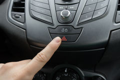 Finger pressing car emergency light button. Man hitting red triangle car hazard warning button stock image