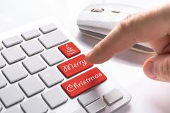 Computer button with Merry Christmas sign. Finger pressing computer button with Merry Christmas sign Royalty Free Stock Photo