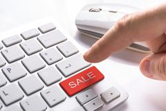 Computer button with sale sign. Finger pressing computer button with red sale sign Stock Images