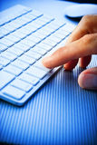 Finger Pressing Computer Keyboard. A close-up of a mans fingers pushing a key on a computer keyboard Royalty Free Stock Image