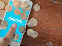 Donation money online by smart phone stock images