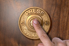 Finger Pressing Doorbell. A male finger pressing a vintage brass doorbell on an  wooden background - 3D render Stock Photo