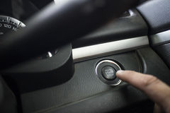 The Finger pressing the Engine start stop button of a car Royalty Free Stock Photography