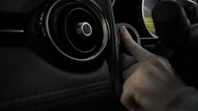 Finger pressing engine stop button of a car.  stock footage