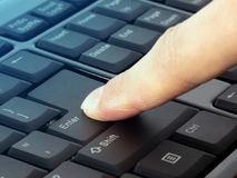 Finger pressing Enter button on the black keyboard stock photos