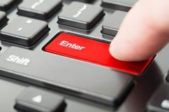 Finger pressing Enter key Stock Image