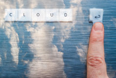 Finger pressing enter key to the cloud Royalty Free Stock Photography