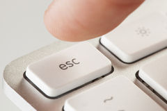 Finger Pressing Escape on a Grey Computer Keyboard Stock Photos