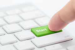 Finger pressing green start button on keyboard. Online begginer succes concept Stock Image