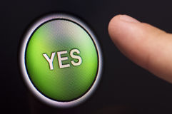 Finger pressing a green YES button on touchscreen. A finger pressing a green YES button on a touchscreen interface Stock Photo