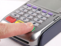 Finger pressing a key on a Payment terminal Stock Image
