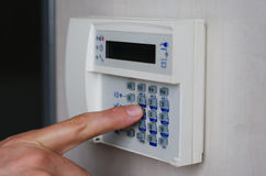 Finger pressing keys on alarm keypad Stock Images