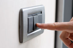 Finger pressing light switch Stock Photo
