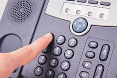 Finger pressing number button on telephone to make a call Stock Images