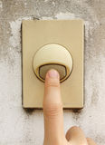 Finger pressing on old door bell switch Royalty Free Stock Images