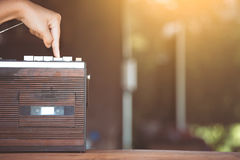 Finger pressing the play bottom on retro radio cassette stereo. In vintage color tone Stock Photos