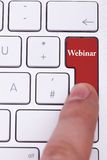 Finger pressing on red webinar button on metallic keyboard stock photography