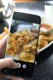 Finger pressing on smartphone for photograph chinese food in res. Taurant, for food ad or website promote Royalty Free Stock Photography