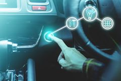 Finger pressing the start/stop engine button on car with busines. S icons for startup concept royalty free stock photos