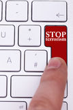 Finger pressing on stop terrorism button on keyboard. Stop the crimes against civil people Royalty Free Stock Image