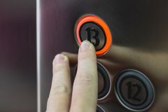Finger pressing thirteenth floor button in elevator. Unlucky n. Umber, fear concept stock photo