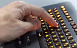 Finger pressing Y key on illuminated industrial ke Stock Photos
