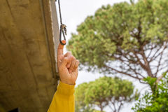 Finger pulling eyelet. Finger pulling the eyelet of a nylon cord under a balcony in the garden stock image