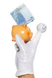 Finger puppet holding piggybank with euro note. Happy finger puppet holding twenty euro note on piggy bank back Royalty Free Stock Image